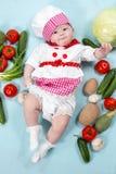 Κορίτσι μαγείρων μωρών που φορά το καπέλο αρχιμαγείρων με τα φρέσκα λαχανικά. Στοκ φωτογραφία με δικαίωμα ελεύθερης χρήσης