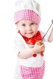 Κορίτσι μαγείρων μωρών που φορά το καπέλο αρχιμαγείρων με τα φρέσκα λαχανικά και τα φρούτα. Στοκ Εικόνα