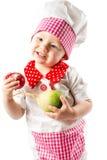 Κορίτσι μαγείρων μωρών που φορά το καπέλο αρχιμαγείρων με τα φρέσκα λαχανικά και τα φρούτα Στοκ Εικόνες
