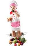 Κορίτσι μαγείρων μωρών που φορά το καπέλο αρχιμαγείρων με τα φρέσκα λαχανικά και τα φρούτα. Στοκ Φωτογραφία