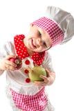 Κορίτσι μαγείρων παιδιών που φορά το καπέλο αρχιμαγείρων με τα φρέσκα λαχανικά Στοκ φωτογραφία με δικαίωμα ελεύθερης χρήσης