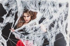Κορίτσι μαγισσών αποκριών cought στο δίκτυο αραχνών σε μια μπλούζα και μια κόκκινη φούστα Στοκ Φωτογραφίες