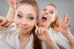 Κορίτσι μανίας που κραυγάζει στο φίλο της, θηλυκό που κλείνει τα αυτιά του Στοκ φωτογραφίες με δικαίωμα ελεύθερης χρήσης