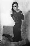 Κορίτσι, μαύρα μακρυμάλλη και μακριά πόδια φορεμάτων στα καλσόν blak και το λευκό Στοκ Εικόνες