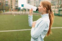 Κορίτσι μετά από να εκπαιδεύσει, να τρέξει ή τον αθλητισμό ένα υπόλοιπο στο πρώτο πλάνο, ένα μπουκάλι νερό Το κορίτσι εργάζεται σ στοκ φωτογραφία με δικαίωμα ελεύθερης χρήσης