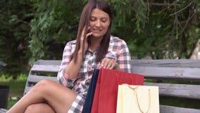 Κορίτσι μετά από να ψωνίσει που μιλούν στην τηλεφωνική συνεδρίαση σε έναν πάγκο στο πάρκο κίνηση αργή HD φιλμ μικρού μήκους
