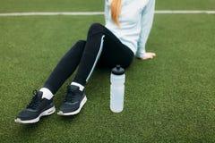 Κορίτσι μετά από την άσκηση, πόσιμο νερό στο αγωνιστικό χώρο ποδοσφαίρου Πορτρέτο του όμορφου κοριτσιού sportswear στοκ φωτογραφία