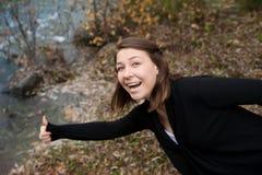 Κορίτσι με έναν αυξημένο αντίχειρα στον ποταμό Στοκ φωτογραφία με δικαίωμα ελεύθερης χρήσης