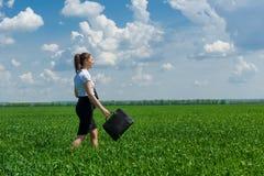 Κορίτσι με έναν χαρτοφύλακα που περπατά στη χλόη Στοκ Φωτογραφίες