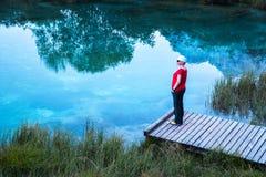 Κορίτσι με ένα άσπρο καπέλο, κόκκινη μπλούζα που στέκεται και που χαλαρώνει σε μια ξύλινη αποβάθρα στοκ φωτογραφία