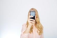 Κορίτσι με ένα έξυπνο τηλέφωνο Απομονωμένος στο λευκό Στοκ Φωτογραφίες