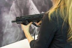 Κορίτσι με ένα αυτόματο τουφέκι στα χέρια του μετρητή όπλο στοκ εικόνες