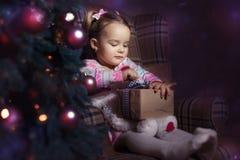 Κορίτσι με ένα δώρο κοντά στο χριστουγεννιάτικο δέντρο Στοκ Εικόνες