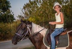 Κορίτσι με ένα καπέλο που οδηγά ένα άλογο στοκ φωτογραφίες