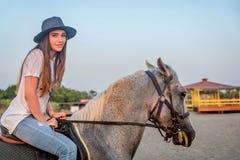 Κορίτσι με ένα καπέλο που οδηγά ένα άλογο στοκ εικόνα