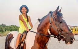 Κορίτσι με ένα καπέλο που οδηγά ένα άλογο στοκ εικόνα με δικαίωμα ελεύθερης χρήσης