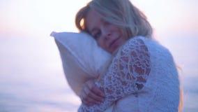 Κορίτσι με ένα μαξιλάρι στην παραλία Ήπια την αγκαλιάζει και εξετάζει τη κάμερα κίνηση αργή φιλμ μικρού μήκους