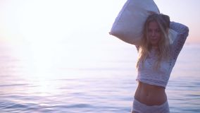 Κορίτσι με ένα μαξιλάρι στην παραλία Ήπια την αγκαλιάζει και εξετάζει τη κάμερα κίνηση αργή απόθεμα βίντεο