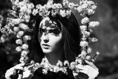 Κορίτσι με ένα πλαίσιο λουλουδιών πλαίσιο εκμετάλλευσης γυναικών των άσπρων, ανθίζοντας λουλουδιών Στοκ Εικόνες