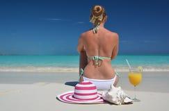 Κορίτσι με ένα ποτήρι του χυμού από πορτοκάλι στην παραλία Στοκ εικόνες με δικαίωμα ελεύθερης χρήσης