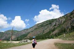 Κορίτσι με ένα σακίδιο πλάτης στα βουνά στο δρόμο Στοκ Φωτογραφίες