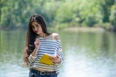 Κορίτσι με ένα σημειωματάριο στο πάρκο κοντά στον ποταμό Στοκ Φωτογραφίες