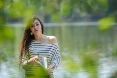 Κορίτσι με ένα σημειωματάριο στο πάρκο κοντά στον ποταμό Στοκ φωτογραφίες με δικαίωμα ελεύθερης χρήσης