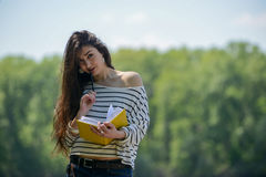 Κορίτσι με ένα σημειωματάριο στο πάρκο κοντά στον ποταμό Στοκ εικόνες με δικαίωμα ελεύθερης χρήσης