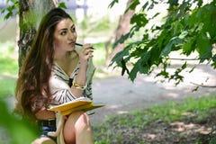 Κορίτσι με ένα σημειωματάριο στο πάρκο κοντά στον ποταμό Στοκ φωτογραφία με δικαίωμα ελεύθερης χρήσης