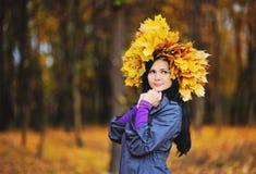 Κορίτσι με ένα στεφάνι από τα κίτρινα φύλλα στο κεφάλι στο backgro Στοκ Φωτογραφίες