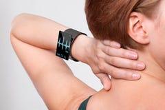 Κορίτσι με ένα σύγχρονο έξυπνο ρολόι Διαδικτύου στο γκρίζο υπόβαθρο στοκ εικόνες