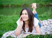 Κορίτσι με ένα τηλέφωνο που στηρίζεται στο χορτοτάπητα Στοκ Φωτογραφίες