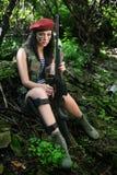 Κορίτσι με ένα τουφέκι στα ξύλα στοκ εικόνα