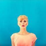 Κορίτσι με ένα hairstyle σε μια μπλε ανασκόπηση Στοκ Εικόνες