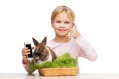 Κορίτσι με λίγο λαγουδάκι στη χλόη και το τηλέφωνο Στοκ Εικόνες