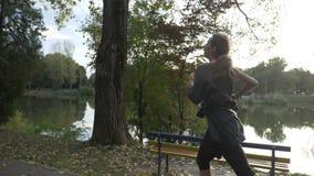 Κορίτσι με λεπτό αριθμού σε ένα πάρκο αλεών κοντά στη λίμνη που προσπαθεί να χαλαρώσει και να μείνει παρακινημένος σε σε αργή κίν φιλμ μικρού μήκους