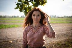 Κορίτσι με μακρυμάλλη σε ένα σλαβικό εκλεκτής ποιότητας φόρεμα της ηλικίας Βίκινγκ κάτω από ένα δρύινο δέντρο στοκ εικόνα με δικαίωμα ελεύθερης χρήσης
