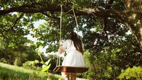 Κορίτσι με μακρυμάλλη στο άσπρο φόρεμα που οδηγά στην ταλάντευση κάτω από ένα δρύινο δέντρο στο πάρκο το φθινόπωρο πίσω όψη κίνησ απόθεμα βίντεο