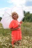 Κορίτσι με μια άσπρη ομπρέλα, ένα μακρύ φόρεμα, ένας τομέας των λουλουδιών, ένα ρόδινο φόρεμα όμορφο ξανθό κορίτσι σε έναν τομέα  Στοκ Εικόνες