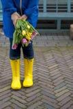 Κορίτσι με μια ανθοδέσμη των τουλιπών άνοιξη στο ροζ Σε ένα μπλε αδιάβροχο και κίτρινες μπότες στην οδό στην Ευρώπη ευτυχής γυναί Στοκ Εικόνες