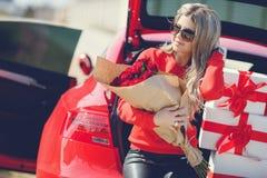Κορίτσι με μια ανθοδέσμη των κόκκινων τριαντάφυλλων κοντά στο αυτοκίνητο Στοκ Φωτογραφία