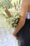 Κορίτσι με μια ανθοδέσμη των wildflowers Στοκ Φωτογραφίες