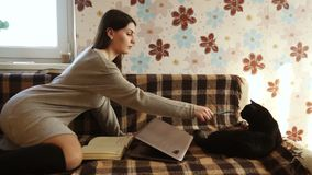 Κορίτσι με μια γάτα που βρίσκεται στον καναπέ απόθεμα βίντεο