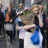 Κορίτσι με μια πλεξούδα στο κεφάλι της Τα αγορασμένα λουλούδια, συζητήσεις στο τηλέφωνο, πηγαίνουν σε Bricklane Στοκ φωτογραφία με δικαίωμα ελεύθερης χρήσης