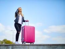 Κορίτσι με μια ρόδινη βαλίτσα σε ένα υπόβαθρο ενός όμορφου μπλε ουρανού Στοκ Εικόνες