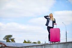 Κορίτσι με μια ρόδινη βαλίτσα σε ένα υπόβαθρο ενός όμορφου μπλε ουρανού Στοκ Εικόνα