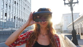 Κορίτσι με μια συσκευή της εικονικής πραγματικότητας στην πόλη απόθεμα βίντεο