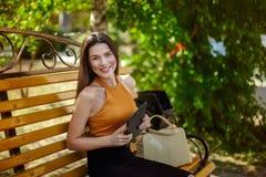 Κορίτσι με μια ταμπλέτα Χαρούμενη και ευτυχής συνεδρίαση επιχειρησιακών γυναικών σε έναν πάγκο με μια τσάντα και μια ταμπλέτα στοκ φωτογραφία