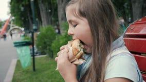 Κορίτσι με μια όρεξη που τρώει ένα χάμπουργκερ απόθεμα βίντεο