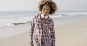 Κορίτσι με τα ακουστικά που περπατά στην παραλία στοκ εικόνες με δικαίωμα ελεύθερης χρήσης